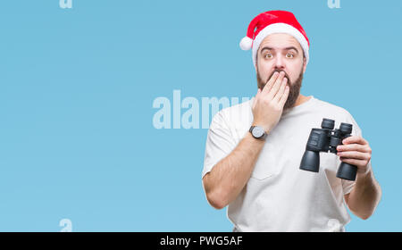 Young caucasian hipster man wearing christmas hat looking though binoculars over isolated background cover mouth with hand shocked with shame for mist - Stock Photo