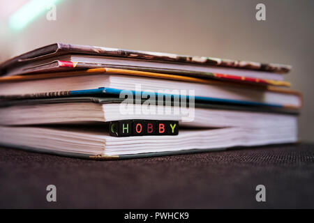 Love of books, reading. Stack of books in the colored cover lay on the table. Open book with curled leaves in the shape of a heart. Library, education - Stock Photo
