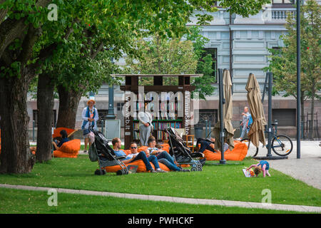 Lithuania people park, view of a family group relaxing near a courtesy bookstand in a corner of Lukiskiu aikste city park in the Vilnius New Town area. - Stock Photo