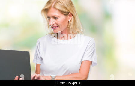 Middle age blonde woman using computer laptop over isolated background with a confident expression on smart face thinking serious - Stock Photo