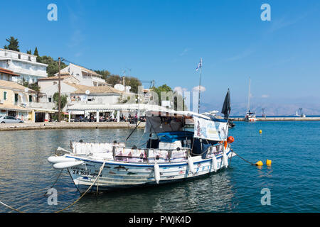 Fishing boats moored in the pretty harbour of Kassiopi in north east Corfu - Stock Photo