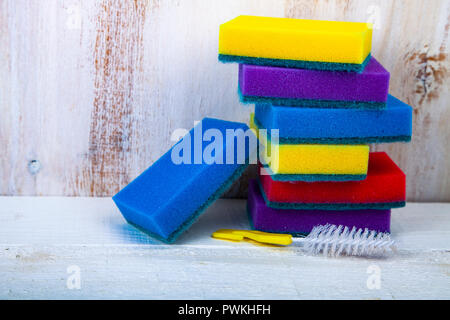 Multi-colored sponges for washing dishes on a wooden background. - Stock Photo