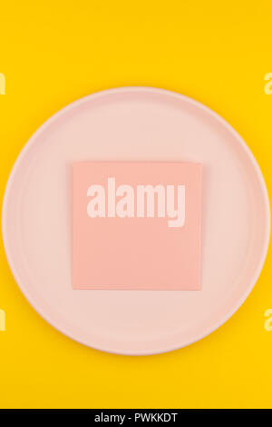 Small love pink letter on plate with serving plastic tableware with copy space on bold yellow background in creative minimal style. Concept template f - Stock Photo