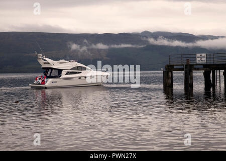 Motor cruiser approaching Luss pier on Loch Lomond in early morning with mist on the hills beyond. - Stock Photo
