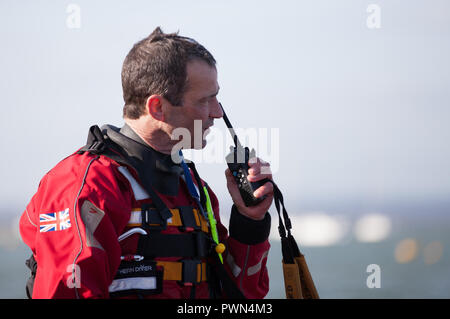 Coast Guard worker on the radio reporting - Stock Photo