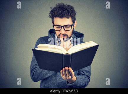 Young man in glasses looking confused while trying to read smart book on gray background - Stock Photo