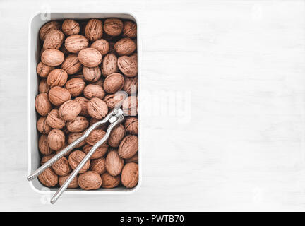 Walnuts and nutcracker in a box, on white painted wooden background with copy space. - Stock Photo