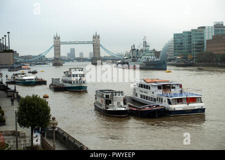 Tourist and Party Boats Moored in the River Thames with HMS Belfast and Tower Bridge in the Background London England United Kingdom UK - Stock Photo