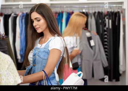 Side view of beautiful young woman standing new hangers and looking for new clothes in store. Brunette choosing new cool outfit before buying. Concept of purchasing and wear. - Stock Photo