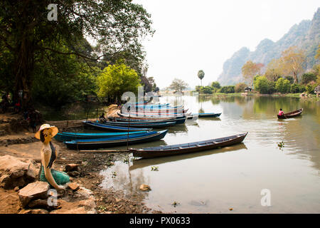 HPA-AN, MYANMAR – MARCH 2018: Lake with boats next to the Sadan cave near Hpa-An in Myanmar - Stock Photo