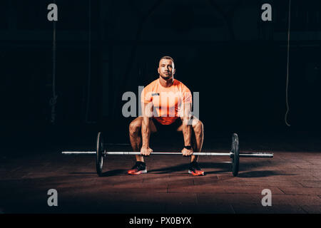 handsome athletic bodybuilder lifting barbell in dark gym - Stock Photo