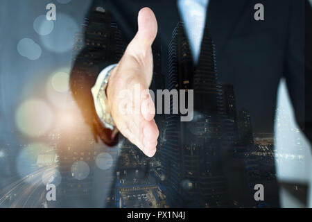 A double exposure shot of a young executive extending his arm for a nahdshake. City scape background - Stock Photo