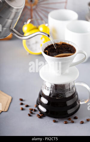 Pour over coffee being made with a kettle and glass carafe with hot water being poured and alarm clock in the background - Stock Photo
