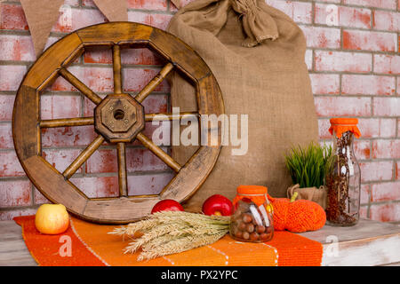 Autumn decoration with red maple leaves, autumn flowers and halloween pumpkins. Fall harvest on brick wall . For holiday post card.Country house design cart wheel, grain bag, nuts, wheat, rye, carpet, thanksgiving day - Stock Photo