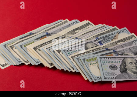 Stack of one hundred dollar bills new and old design on red background. casino bet - Stock Photo