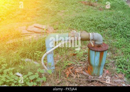 Water valve Plumbing pipe Steel dilapidated on grass. old rusty industrial tap with sunset light tone. - Stock Photo