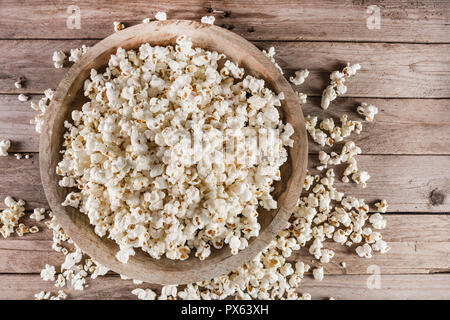 Top view of popcorn in wooden bowl and retro rustic desk. Popcorn spilled on wooden plank. Close up, selective focus - Stock Photo