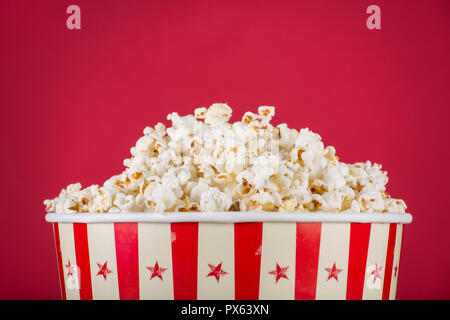 Popcorn in retro box isolated on red background. Movie and cinema food concept. Close up, selective focus - Stock Photo