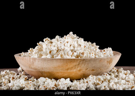 Popcorn in retro wooden bowl and spilled on wooden desk and black background. Food concept. Close up, selective focus - Stock Photo