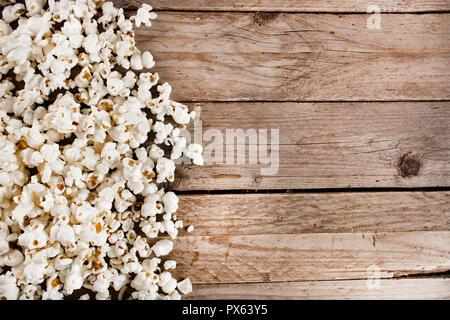 Spilled popcorn on wooden and retro desk and space for design and text. Retro and vintage food concept. Close up, selective focus - Stock Photo