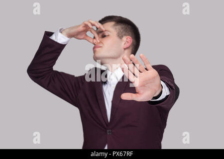 Portrait of handsome confused young man in violet suit and white shirt, standing, blocking his nose and showing stop gesture. focus on hand. indoor st - Stock Photo