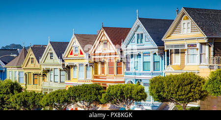 Classic postcard view of famous Painted Ladies, a row of colorful Victorian houses located near scenic Alamo Square, on a beautiful sunny day with blu - Stock Photo