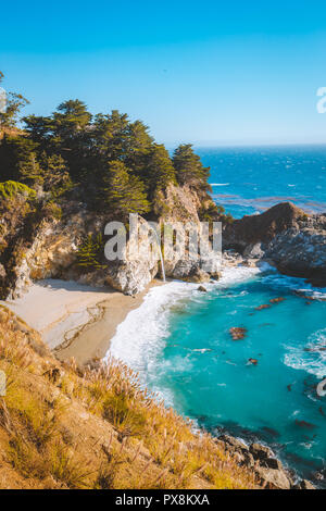 Classic postcard view of famous McWay Falls in scenic golden evening light at sunset on a beautiful sunny day with blue sky in summer, California, USA - Stock Photo