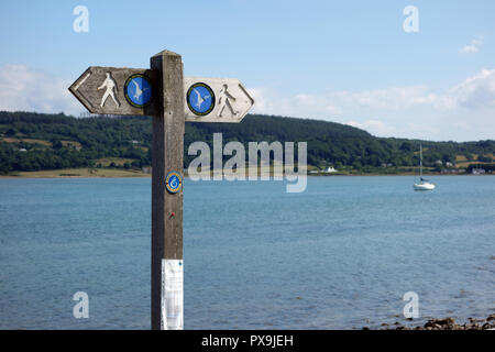 Wooden Signpost for the Isle of Anglesey Coastal Path in Red Wharf Bay, Wales, UK. - Stock Photo