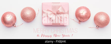 Christmas banner. Beautiful pink christmas gift and ornament baubles isolated on white background. Wrapped xmas box. - Stock Photo