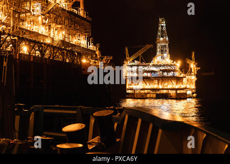 FPSO tanker vessel near Oil platform Rig at night. Offshore oil and gas industry - Stock Photo