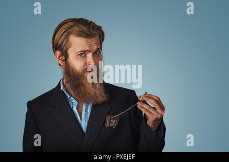 Bearded hipster Businessman looking skeptical holding retro pocket watch Isolated on blue Background. Negative face expression, human emotion, body la - Stock Photo