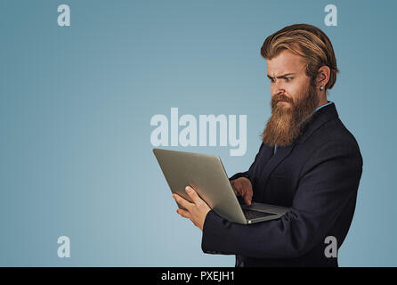 Portrait young unhappy shocked man looking at laptop computer. Bearded hipster businessman Isolated on blue studio Background. Negative face expressio - Stock Photo