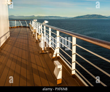 South facing view of port side deck and railing on on a cruise ship in late afternoon light, Dixon entrance, Inside Passage, British Columbia, Canada. - Stock Photo