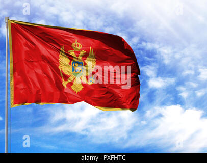 National flag of Montenegro on a flagpole in front of blue sky. - Stock Photo