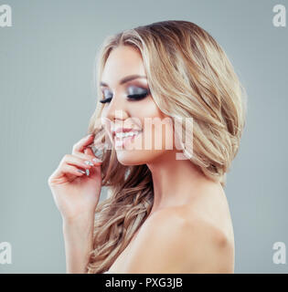 Fashion portrait of young perfect blonde woman with long curly hairstyle and makeup - Stock Photo