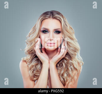 Fashion portrait of young blonde woman with long curly hair and makeup - Stock Photo