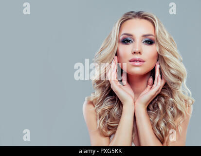 Healthy blonde woman with long curly hair and makeup on blue background - Stock Photo
