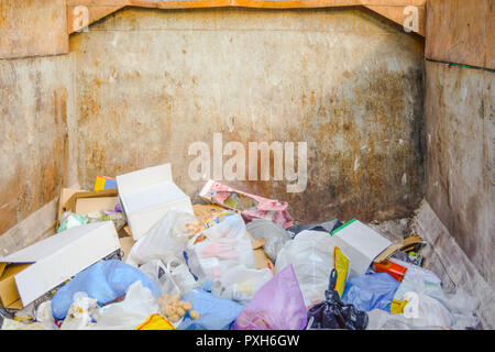 Garbage container with rubbish inside. Garbage from food waste, cans, plastic bottles and plastic bags in large rusty metal dumpster as illustration o - Stock Photo