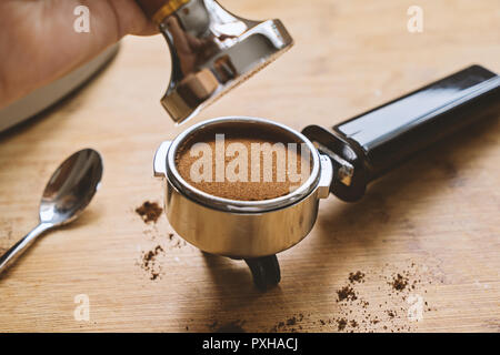 Top view of portafilter with ground coffee and hand hold tamper and press. Making coffee in barista concept - Stock Photo