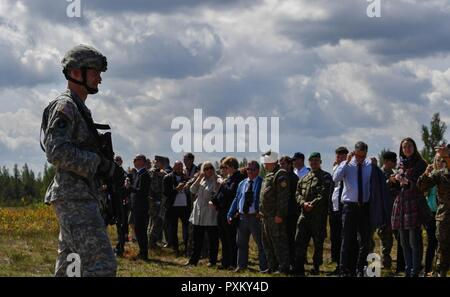 U.S Army National Guard Maj. Michael Nysse, 3rd Battalion, 157th Field Artillery operations officer, speaks to crowd of U.S and NATO distinguished visitors during exercise Saber Strike 17 at Adazi Military Base, Latvia, June 8, 2017. The guests saw a U.S. Marine Corps operation as well as a U.S. Air Force B-52 Stratofortress, B-1B Lancer, two F-16 Fighting Falcons, and two U.S. Army AH-64 Apache helicopters fly overhead during their visit. Saber Strike 17 continues to increase participating nations' capacity to conduct a full spectrum of military operations. - Stock Photo