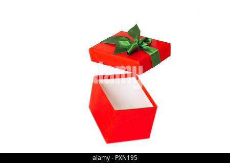 Red gift box with the green satin ribbon and open cover flying on the air - Stock Photo