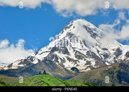 Mount Kazbek (5047m), the third-highest peak in Georgia, bordering Russia, with the Gergeti Trinity Church on its slopes. Khevi-Kazbegi region. Georgia, Caucasus - Stock Photo