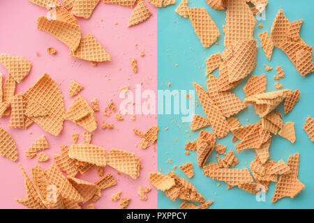 Crushed ice cream waffle cones on pastel pink and blue background, top view flat lay modern minimal composition - Stock Photo