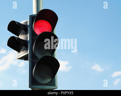 traffic light with red light and blue sky in background. - Stock Photo