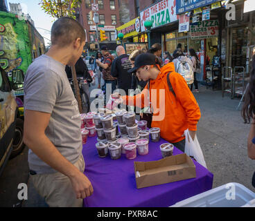 Excited passer-by grab free pint containers of Enlightened- 'The Good-For-You Ice Cream' brand ice cream at a branding event in the New York neighborhood of Chelsea on Friday, October 12, 2018. Enlightened is one of several ice cream brands that include Halo Top, Arctic Zero, among others that promise consumers the indulgence of being able to eat a whole pint, especially when depressed, while retaining the taste of full fat ice cream.  Häagen-Dazs, a premium brand of generally full fat ice cream, is the best selling ice cream by the pint in America. (© Richard B. Levine) - Stock Photo