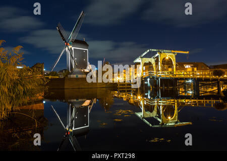 Mill de Put and the rembrandt bridge in Leiden by night and reflection in the river Rijn in LEIDEN, THE NETHERLANDS - Stock Photo