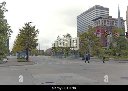 A couple people cross Superior Avenue in desolate downtown Cleveland Public Square where the city created a controversial bus-only thoroughfare. - Stock Photo