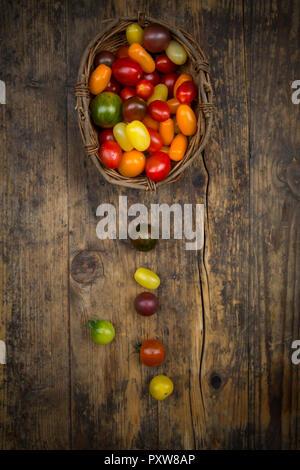 Basket of Heirloom tomatoes on wood - Stock Photo