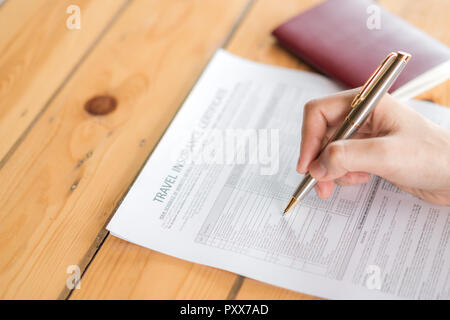 Hand with pen over  Travel Aviation Insurance application form and passport - Stock Photo