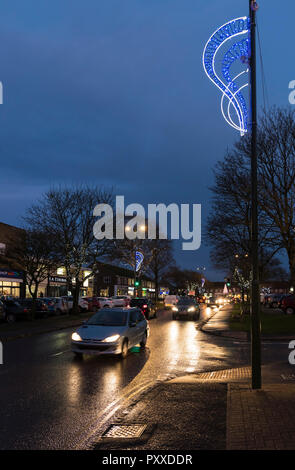 Cars on a British road at night in Winter with Christmas lights displayed in Rustington, West Sussex, England, UK. - Stock Photo